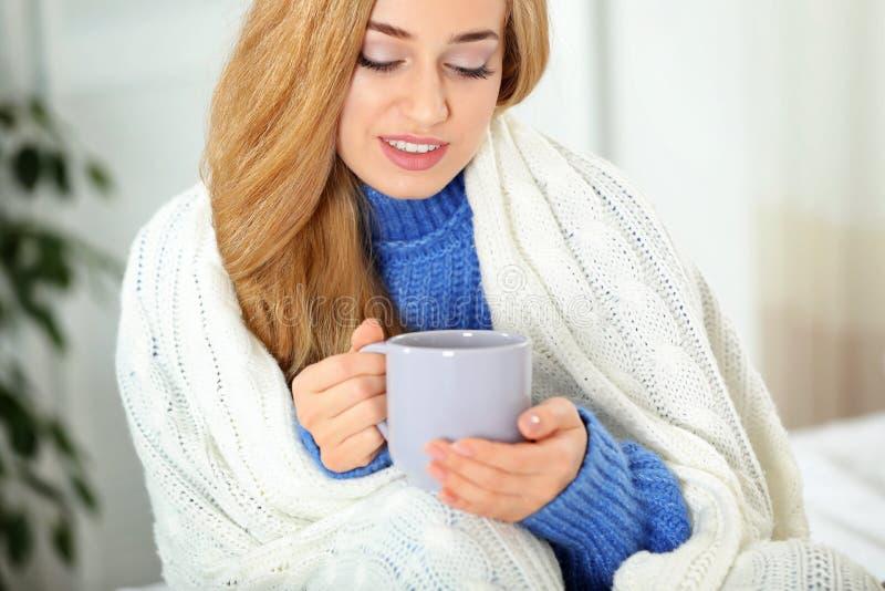 舒适温暖的毛线衣的可爱的年轻女人有杯子的热的饮料和格子花呢披肩 库存图片