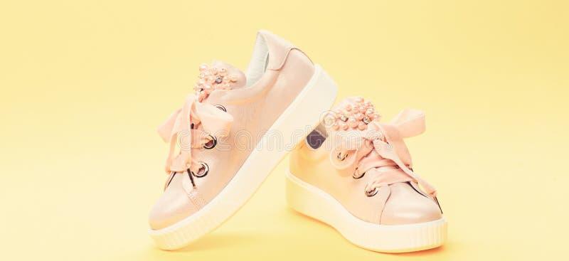 舒适的鞋类概念 在黄色背景的逗人喜爱的鞋子 用珍珠或妇女的鞋类装饰的女孩成串珠状 免版税库存照片