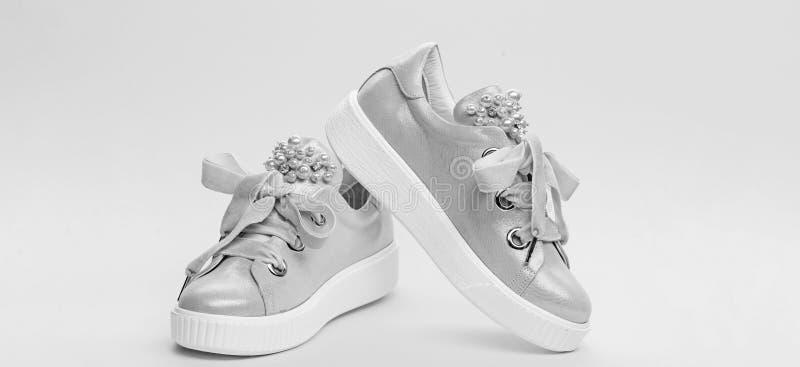 舒适的鞋类概念 在黄色背景的逗人喜爱的鞋子 用珍珠或妇女的鞋类装饰的女孩成串珠状 免版税库存图片