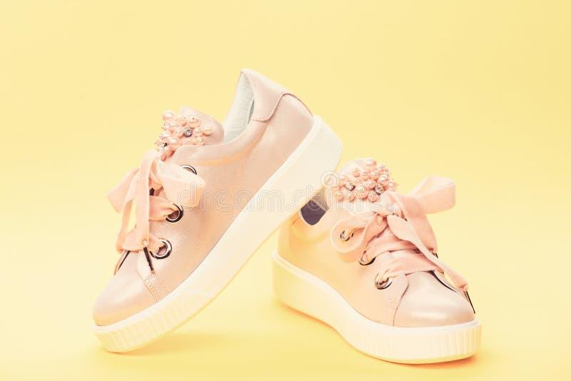 舒适的鞋类概念 用珍珠或妇女的鞋类装饰的女孩成串珠状 对淡粉红的女性运动鞋 免版税库存图片