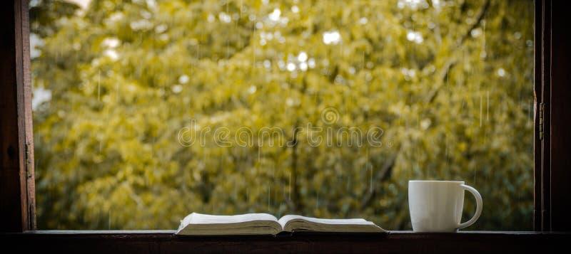 舒适秋天静物画:杯子热的咖啡和被打开的书在葡萄酒窗台和雨外面 秋天 任何地方 雨 免版税库存照片