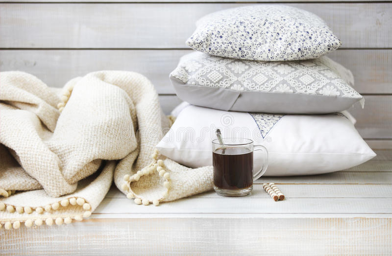 舒适静物画用咖啡、枕头和格子花呢披肩 库存图片