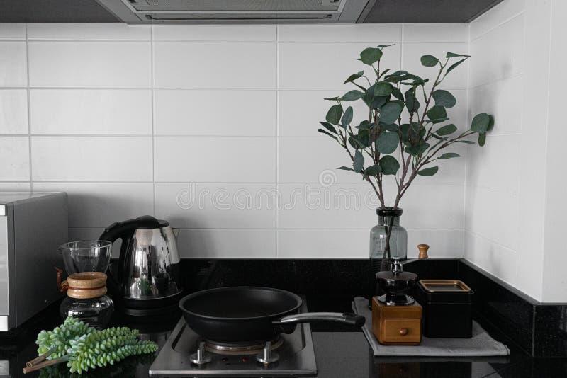 舒适餐具室角落/厨房斯堪的纳维亚样式白色砖瓦片装饰的和人为植物灰色玻璃花瓶的用手c 库存照片