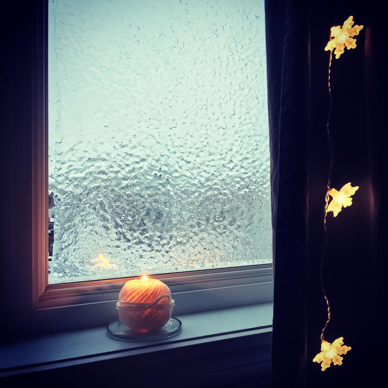舒适结霜的窗口和蜡烛光 库存图片