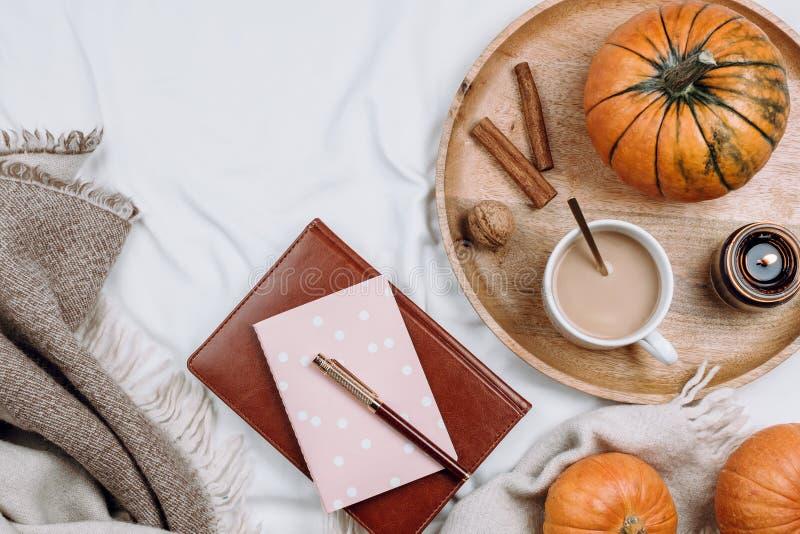 舒适flatlay与木盘子、咖啡或可可粉,蜡烛,南瓜,笔记本 库存图片