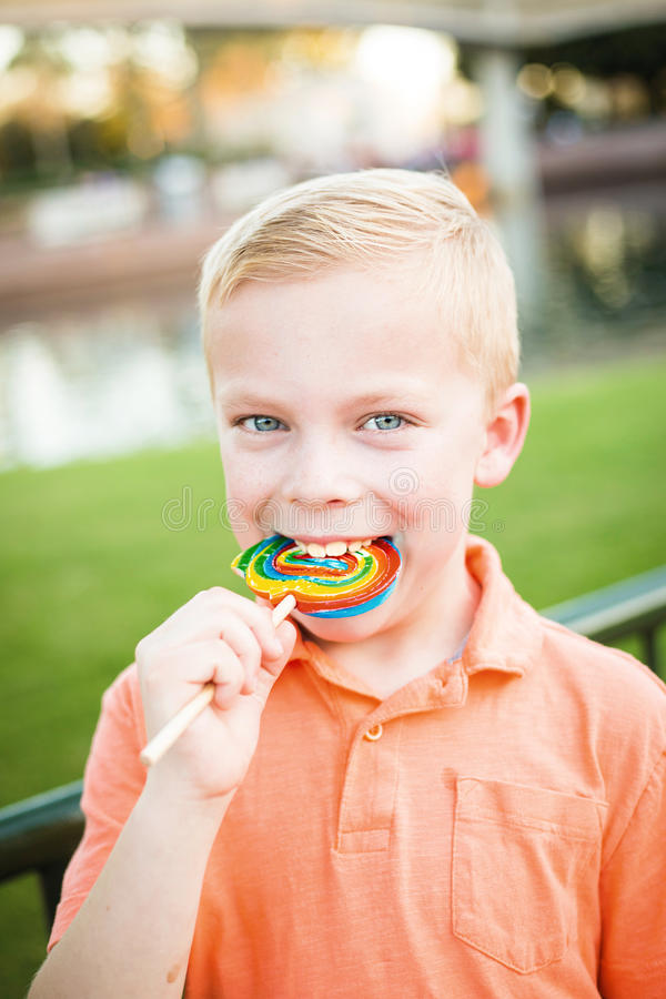 舔一个大五颜六色的棒棒糖的逗人喜爱的年轻男孩户外 免版税库存图片
