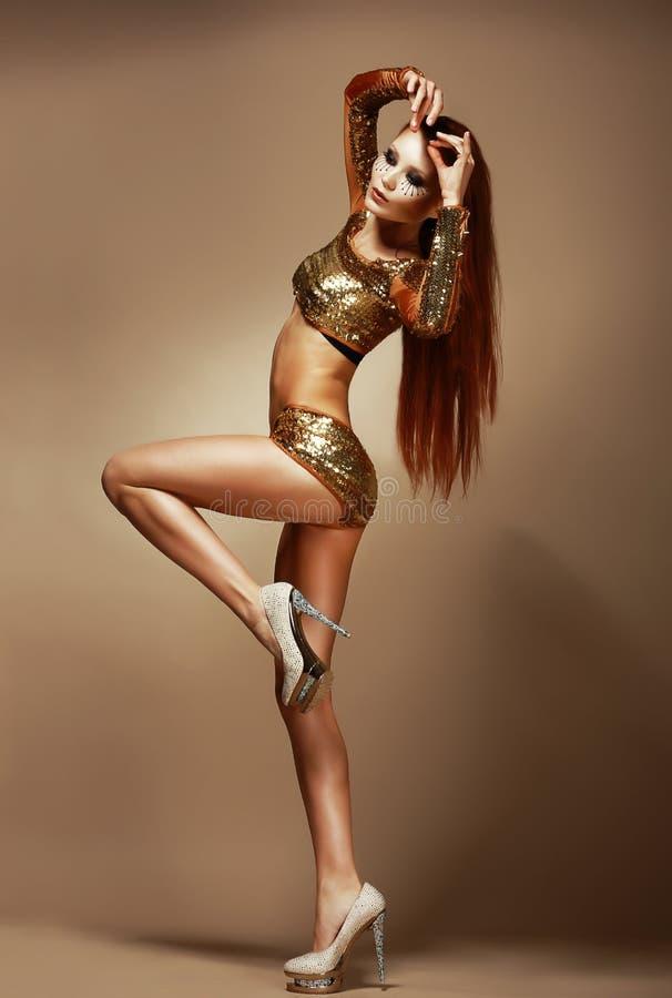 舞蹈。夜总会。金黄比基尼泳装的华美的红头发人妇女。化装舞会服装党 免版税库存图片