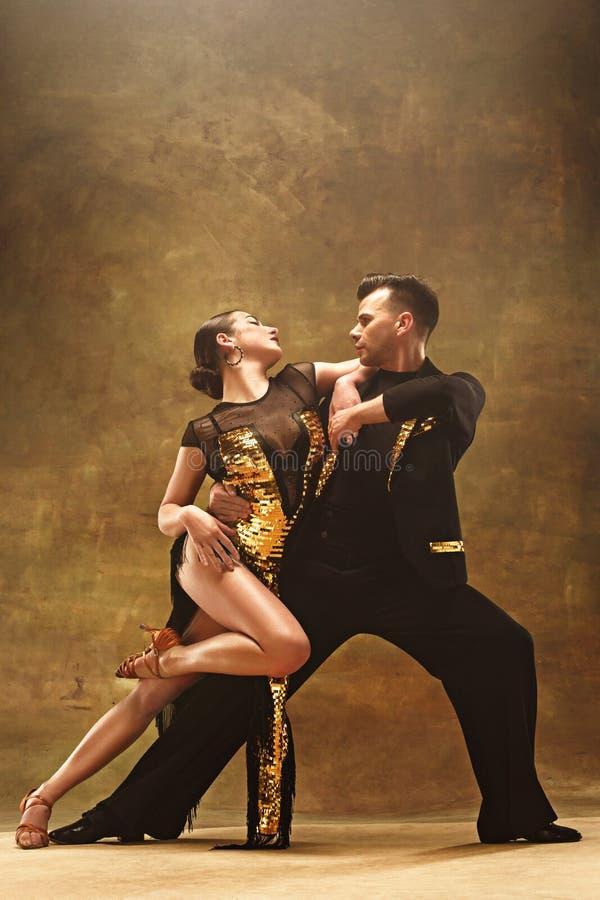 舞蹈在金子的舞厅夫妇穿戴在演播室背景的跳舞 免版税图库摄影