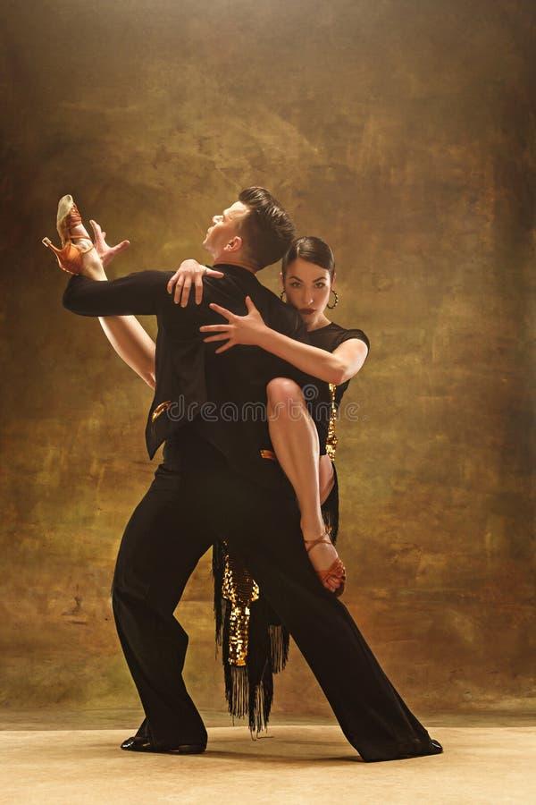 舞蹈在金子的舞厅夫妇穿戴在演播室背景的跳舞 免版税库存图片