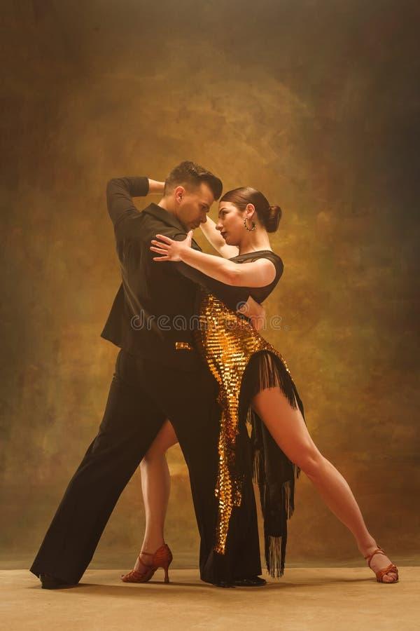 舞蹈在金子的舞厅夫妇穿戴在演播室背景的跳舞 免版税库存照片