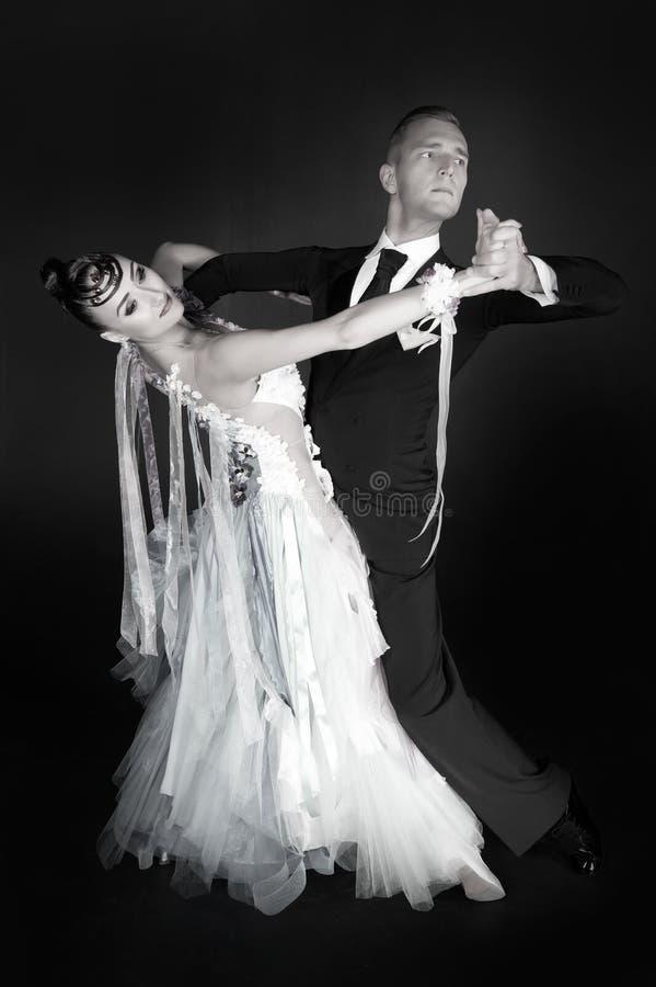 舞蹈在黑背景在红色礼服舞蹈姿势的舞厅夫妇隔绝的 跳舞walz,探戈的肉欲的专业舞蹈家,慢 免版税库存图片