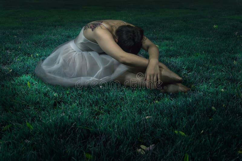 舞蹈家妇女坐夜草场面 免版税库存照片