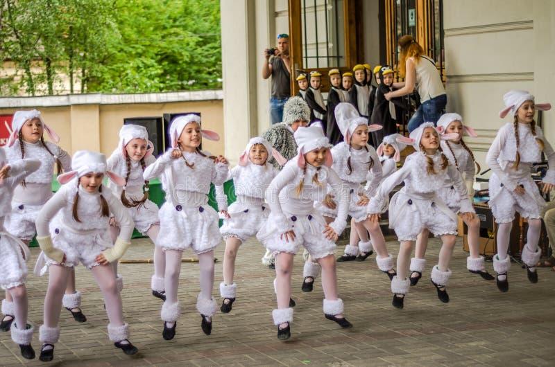 舞蹈小组幼儿舞蹈家执行在作为企鹅和鸟穿戴的观众前面的小孩子的党 库存照片