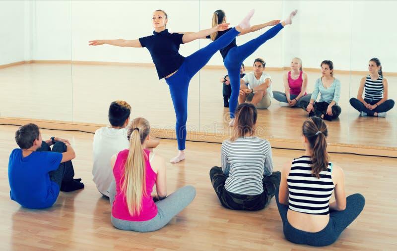 舞蹈老师展示芭蕾位置 免版税图库摄影