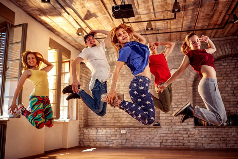 舞蹈队-跳跃在音乐期间的愉快的舞蹈朋友 免版税图库摄影