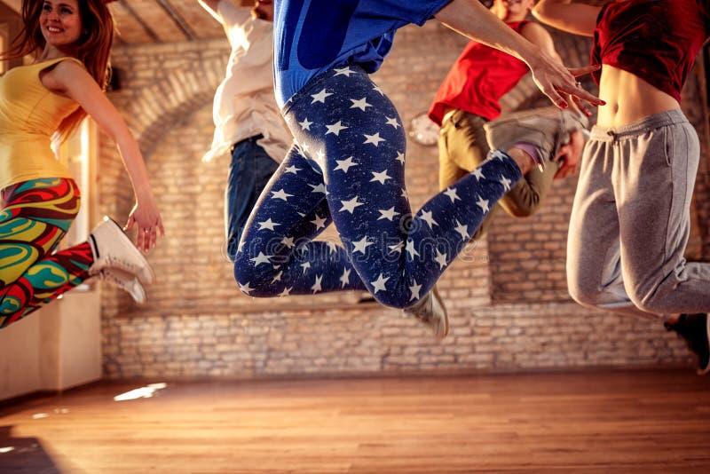 舞蹈队-跳跃在音乐期间的朋友 库存照片