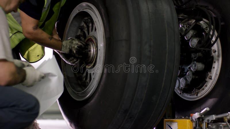 航空器闸修理 关闭飞机轮子和轴 与轴和飞机起落架的巨大的飞机轮胎  免版税图库摄影