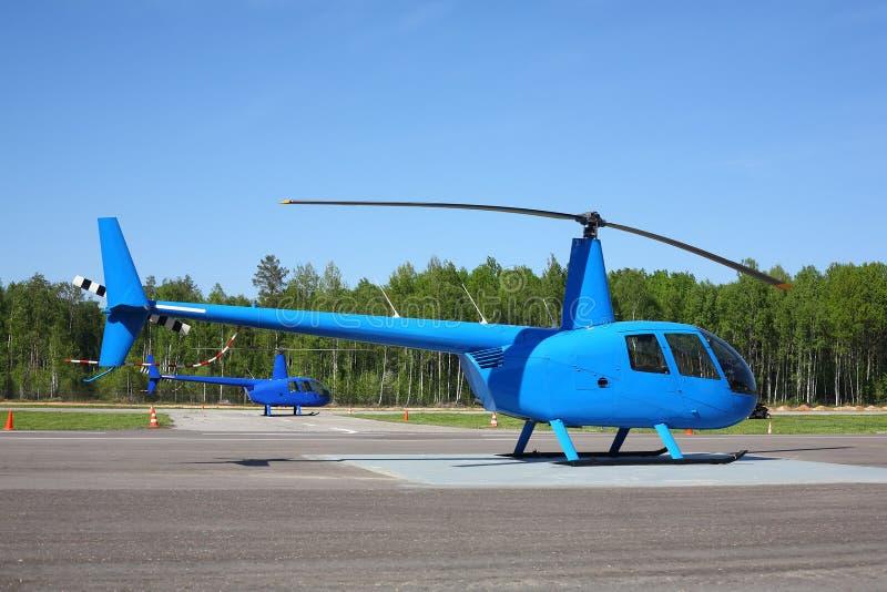航空器-两小蓝色直升机侧视图 免版税库存照片