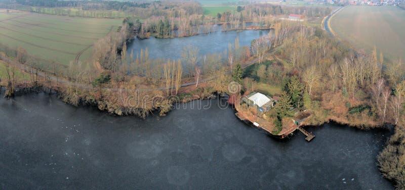 航空摄影和两个小池塘空中照片综合全景在草甸和领域之间的与格栅小屋和鱼 免版税库存图片