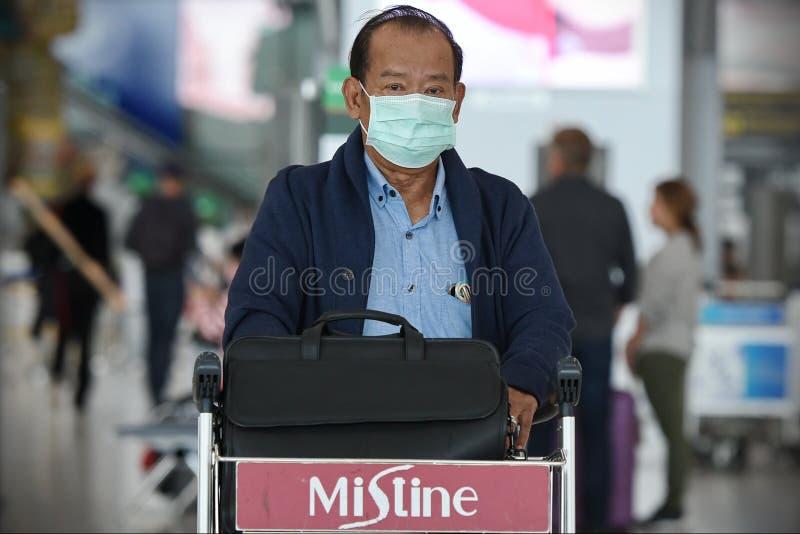 航空旅客戴口罩预防冠状病毒引起的Covid-19 免版税图库摄影