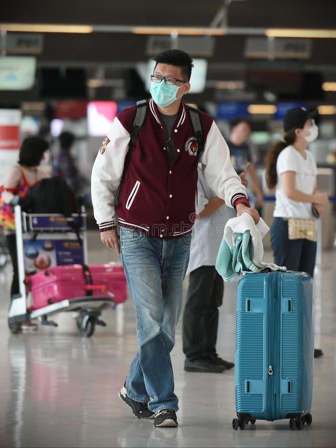 航空旅客戴口罩预防冠状病毒引起的Covid-19 图库摄影