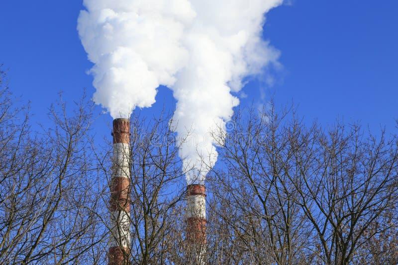 航空背景蓝色工厂污染 管子和干燥树烟反对天空蔚蓝背景 免版税库存图片