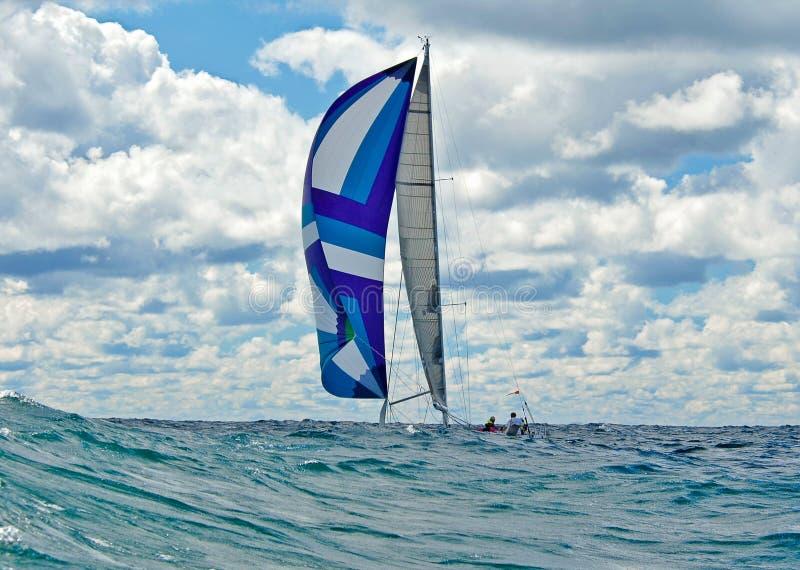 航行与一艘五颜六色的大三角帆 免版税图库摄影