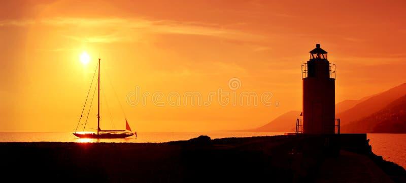 航行和灯塔剪影在日落 免版税库存照片