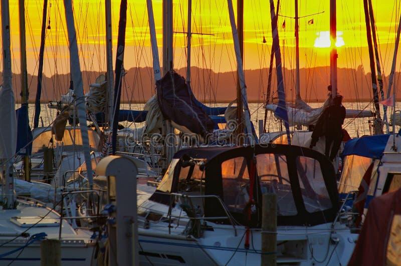 航行在小游艇船坞乘快艇在与索具的日落现出轮廓反对晚上天空 免版税库存图片