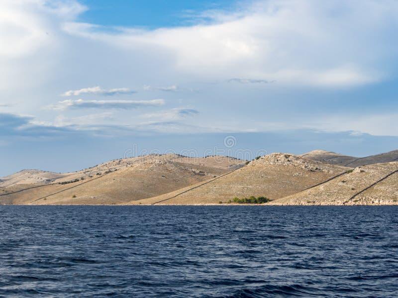 航行在沿岩石和波浪荒岛风景的一条游艇在科纳提群岛国家公园在夏天克罗地亚,地中海 库存图片