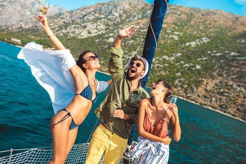 航行在游艇-假期、旅行、海、友谊和人概念的朋友 图库摄影