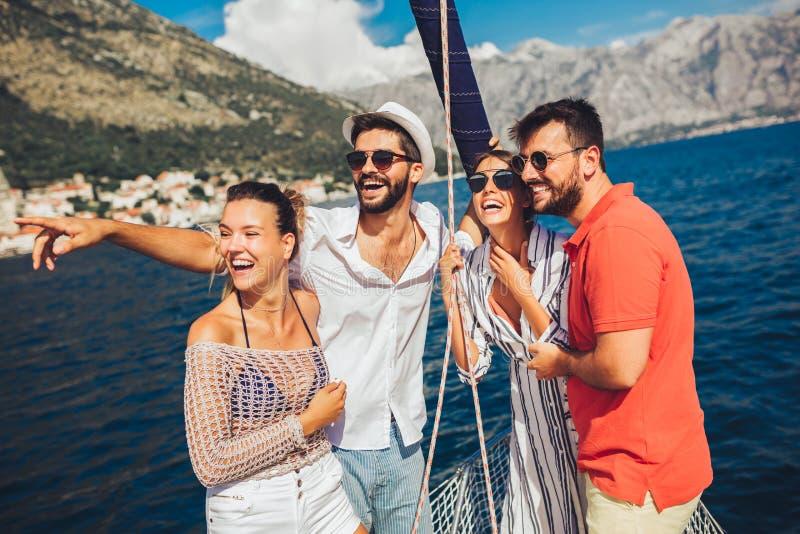 航行在游艇-假期、旅行、海、友谊和人概念的朋友 免版税图库摄影