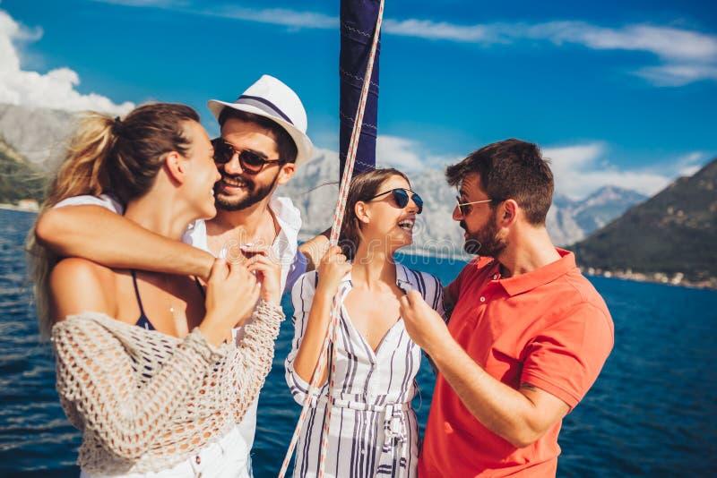 航行在游艇-假期、旅行、海、友谊和人概念的朋友 库存图片