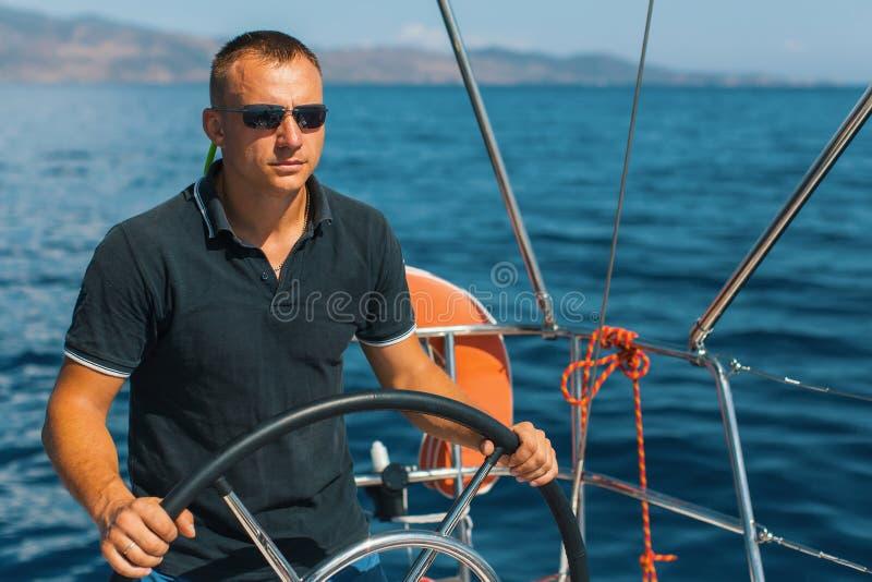 航行游艇的舵的被晒黑的男性船长 库存照片