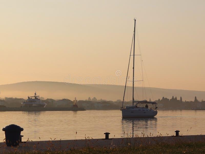 航行游艇输入在马达下在小游艇船坞在早晨太阳的光芒 在口岸的黎明 空的码头与 免版税库存照片