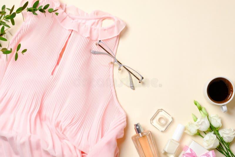 舱内甲板位置女性辅助部件,香水瓶,玫瑰花,桃红色礼服,玻璃,咖啡杯,顶视图秀丽博客作者书桌与 库存图片