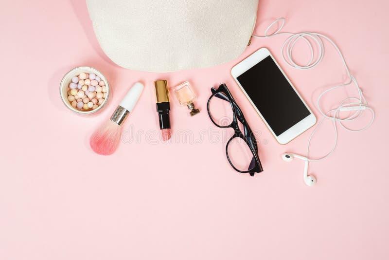舱内甲板位置女性辅助部件:化妆用品,玻璃,手机,耳机,在粉红彩笔背景的构成 库存照片