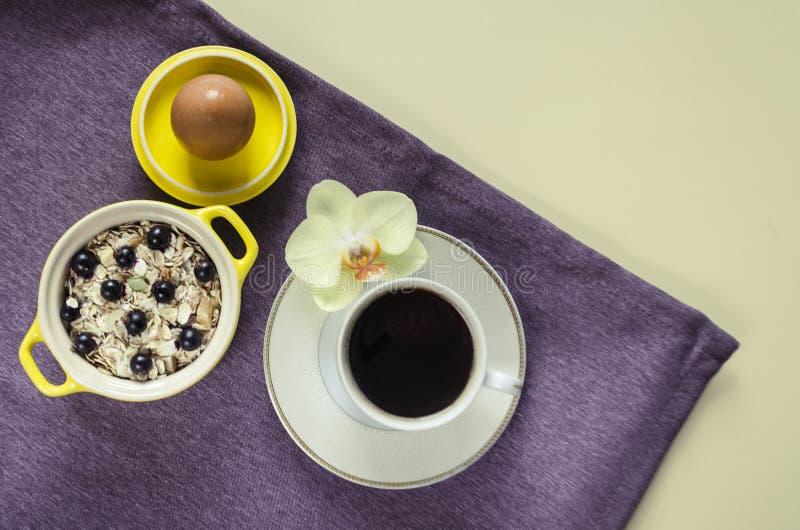 舱内甲板在一个黄色罐的一个盘子燕麦粥,muesli用新鲜的蓝莓,鸡蛋,一块紫色餐巾的咖啡美国人放置在一桃红色backg 库存照片