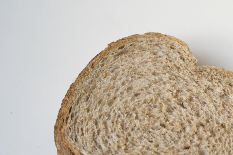 舱内甲板在白色书桌上的被放置的棕色全麦面包 免版税图库摄影