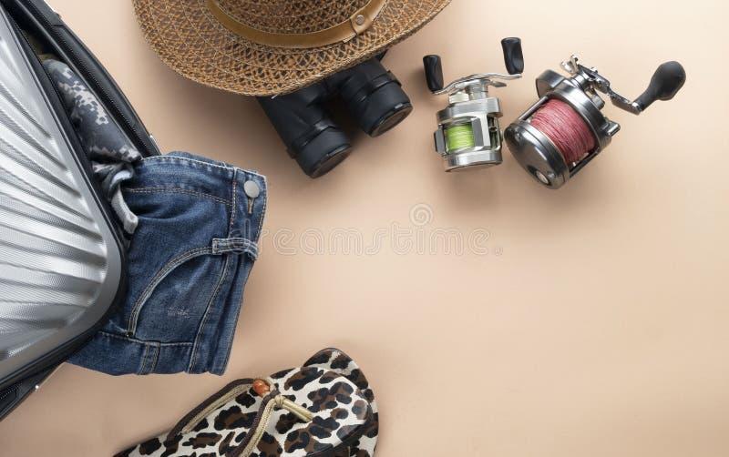 舱内甲板有双筒望远镜的被放置的灰色手提箱,帽子,牛仔裤,转动为钓鱼和凉鞋在淡色背景 旅行概念-图象 库存照片
