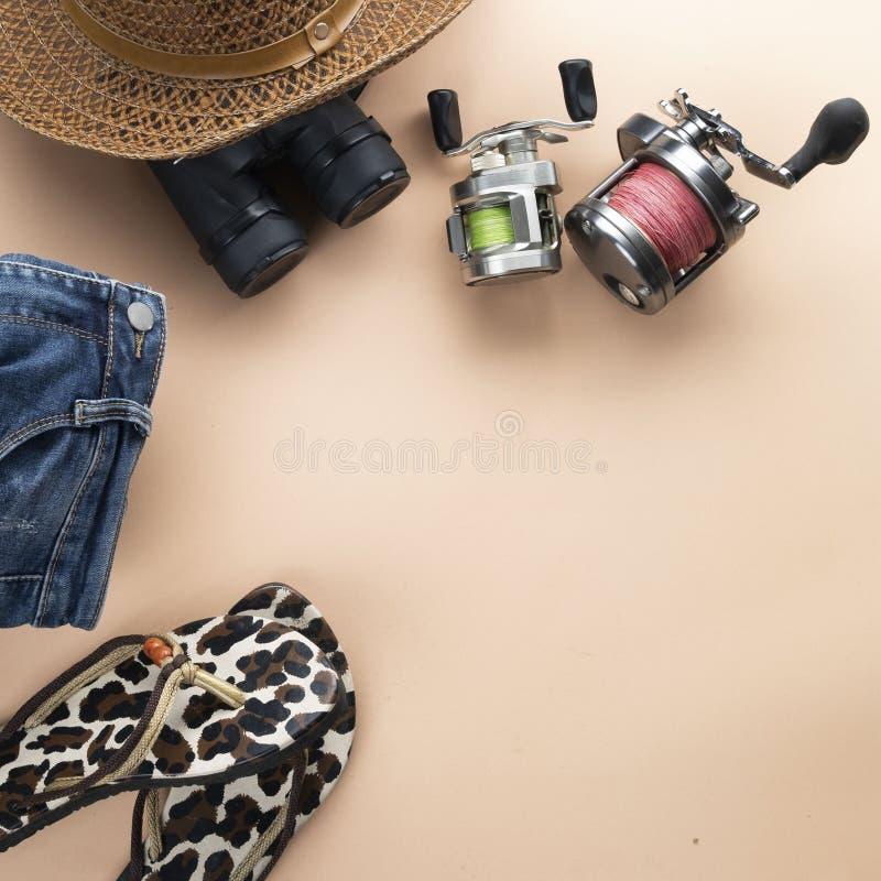 舱内甲板有双筒望远镜的被放置的灰色手提箱,帽子,牛仔裤,转动为钓鱼和凉鞋在淡色背景 旅行概念-图象 免版税库存图片