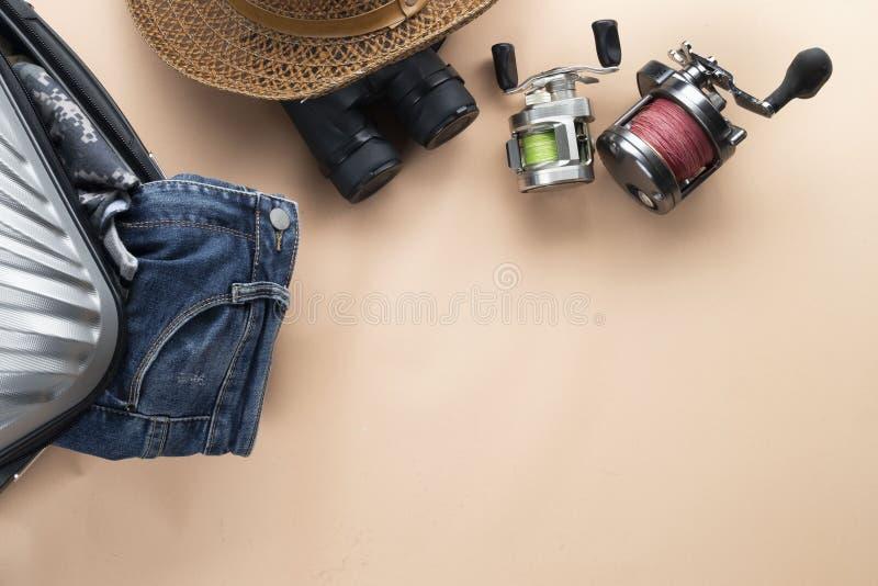 舱内甲板有双筒望远镜的被放置的灰色手提箱,帽子,牛仔裤,转动为钓鱼和凉鞋在淡色背景 旅行概念-图象 图库摄影