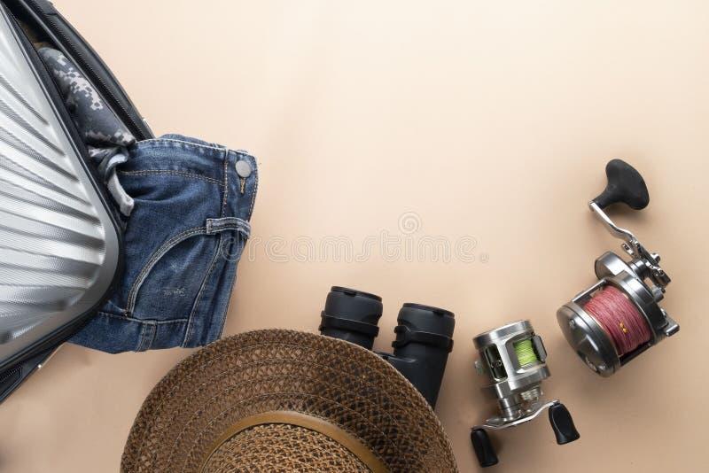 舱内甲板有双筒望远镜的被放置的灰色手提箱,帽子,牛仔裤,转动为钓鱼和凉鞋在淡色背景 旅行概念-图象 库存图片