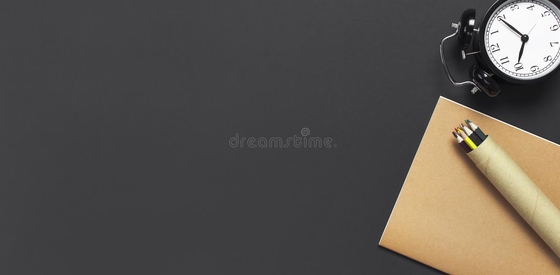 舱内甲板被放置的黑闹钟,练习本笔记本日志,在灰色黑暗的背景顶视图拷贝空间的颜色铅笔 概念时间 库存图片