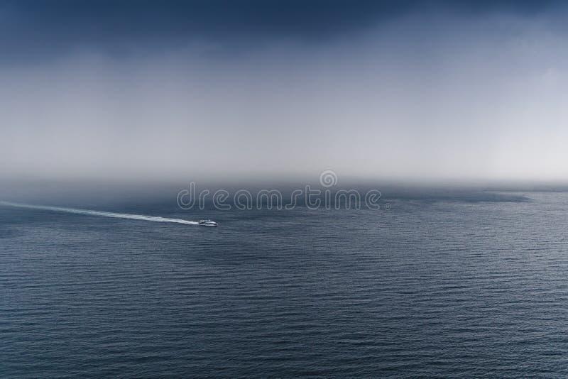 船从雨逃脱,从恶劣天气和大波浪,入海以风雨如磐的多雨云彩为背景, 库存图片