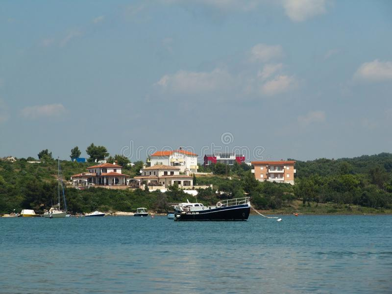 船和小船在与典型的欧洲别墅的岸附近被停泊海湾的美丽的景色 库存图片