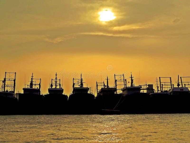 船和日落剪影在吉大港,孟加拉国港  免版税库存照片
