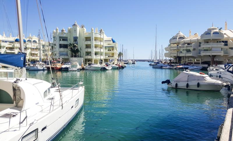 船和白色豪华公寓在小游艇船坞海湾Benalmadena,西班牙 免版税库存图片