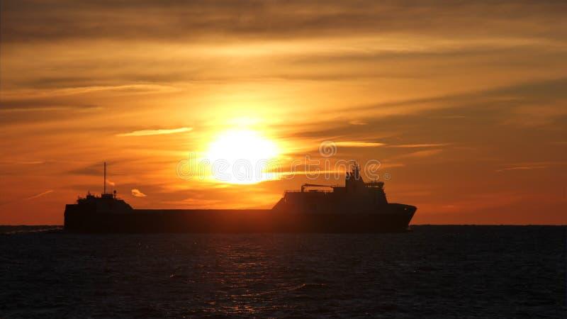 船在反对美好的日落的背景的海 r ?? ?? 库存照片
