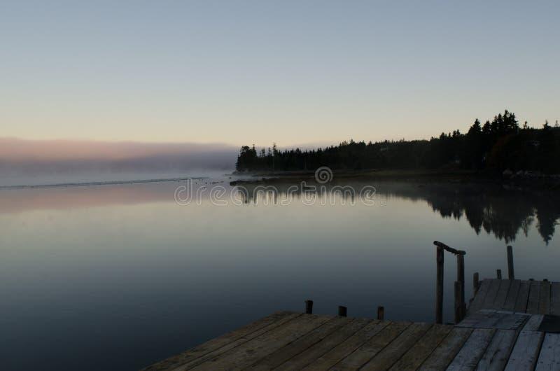船坞leead的线对反射海湾的镇静水的现出轮廓的树木丛生的跳船的 库存照片